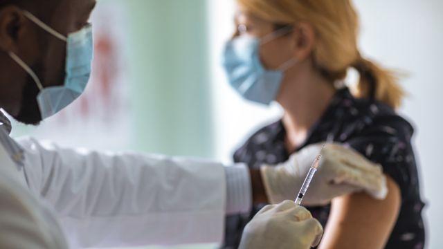 醫生為年輕女子打疫苗針