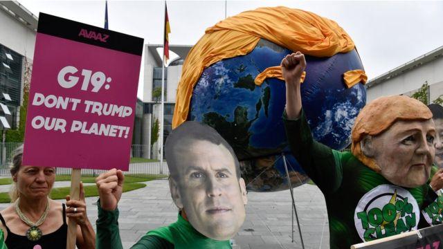 Активисты в масках Ангелы Меркель, Си Цзиньпина и Эммануэля Макрона и шар в виде Земли с прической Трампа в Берлине, июнь 2017 года. В руках у одного из активистов лозунг: G19: Don't Trump our Planet.