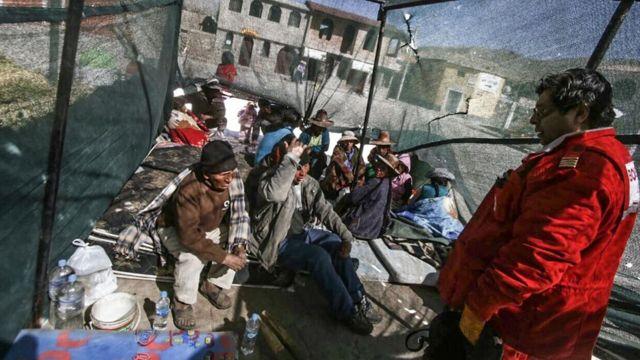 Bombero conversa con los damnificados por el sismo.