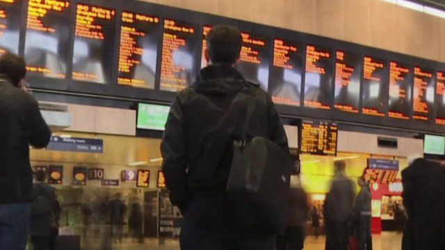 Passengers looking at train departure boards