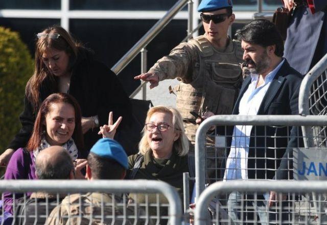 Beraat eden sanıklardan Ayşe Mücella Yapıcı zafer işareti yapıyor