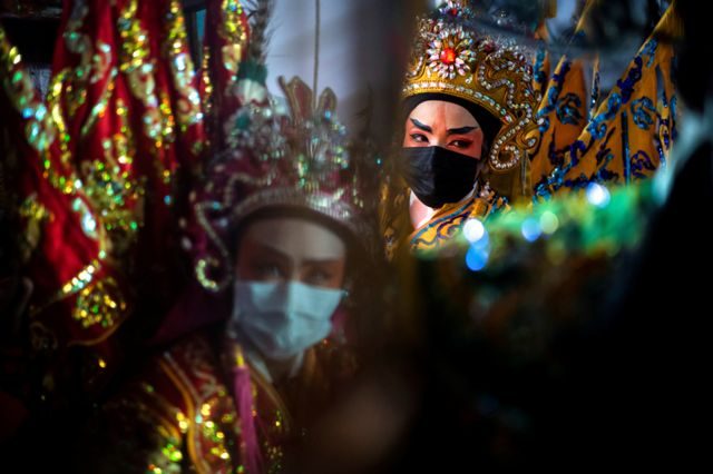 Members of a Chinese opera troupe prepare before performing at a shrine during the annual vegetarian festival in Bangkok, Thailand, 6 October 2021.