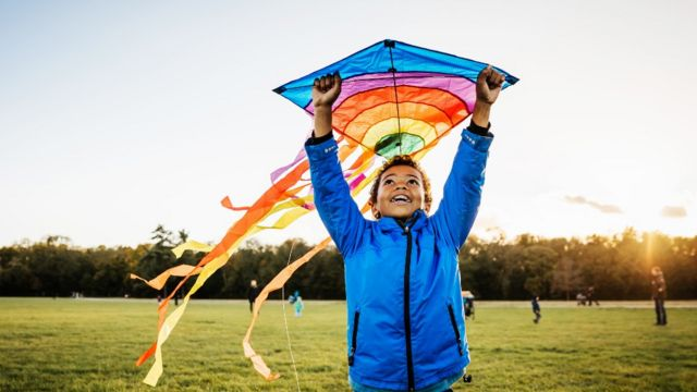 Um menino brincando com uma pipa em um parque