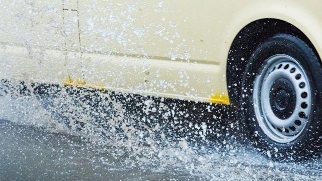 La rueda de un auto pasando por arriba de un charco de agua