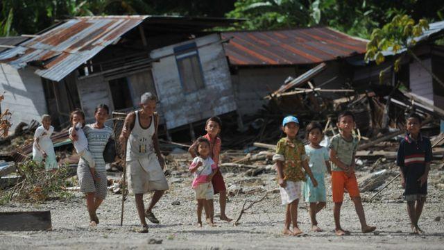 Penduduk Desa Tumalei di Pulau Mentawai berjalan di depan rumah mereka yang hancur pada 31 Oktober 2010, enam hari setelah gempa dengan skala 7,7 SR yang memicu tsunami di kawasan tersebut.