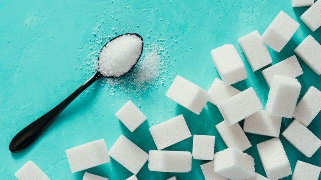 Cubos de açúcar e uma colher cheia com o produto