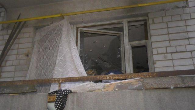 Квартира жінки, яка зносить додому сміття. У вікнах немає скла, вони завішані брудною фіранкою, на стінах - сліди нещодавньої пожежі, яку влаштувала жінка.