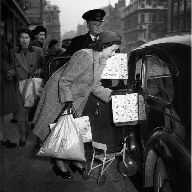 Mujer entra a un coche después de hacer compras