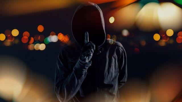 Hombre con el rostro cubierto que hace la señal de silencio.