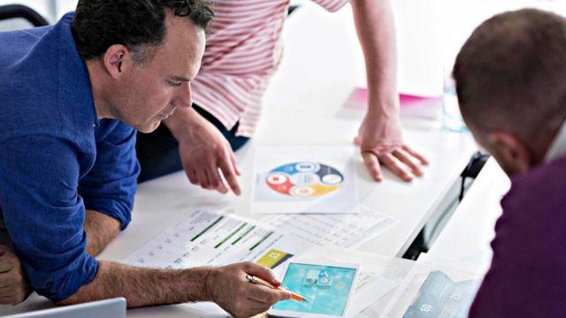 Tres personas discutiendo sobre papeles en una mesa de trabajo