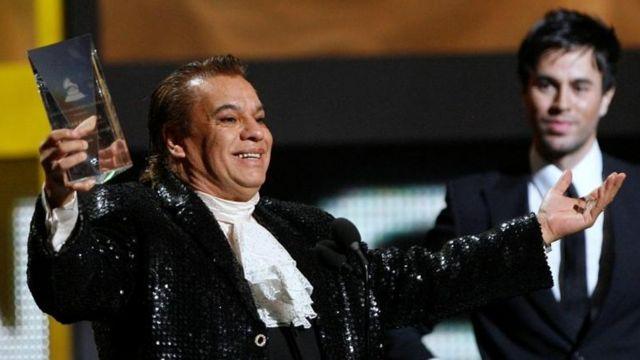 Juan Gabriel saluda con un premio en su mano.