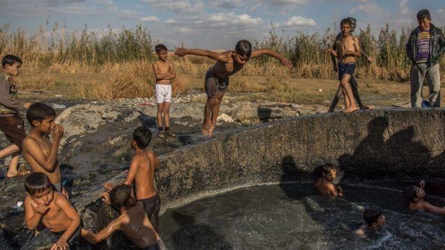 أطفال يسبحون في ينبوع دافيء