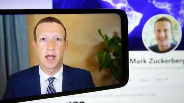 """الرئيس التنفيذي لشركة فايسبوك، مارك زوكربيرج، على شاشة الهاتف المحمول وهو يدلي بشهادته عن بُعد أثناء جلسة استماع للجنة التجارة والعلوم والنقل التابعة لمجلس الشيوخ الأمريكي بعنوان """"هل تمكّن الحصانة الكاسحة للقسم 230 من السلوك السيئ للتكنولوجيا الكبيرة؟"""" في مبنى الكابيتول هيل في واشنطن العاصمة بالولايات المتحدة."""