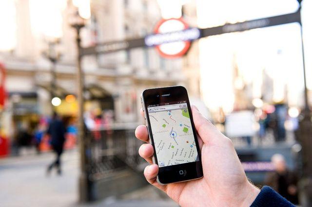 Hombre sostiene un iPhone en el que tiene activado Google Maps en una calle de Londres.