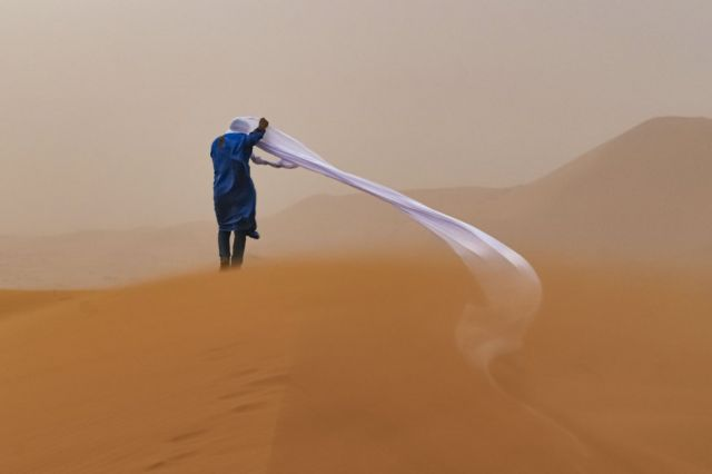 A man struggles with wind blowing at cloth around his head whilst standing in the Sahara Desert