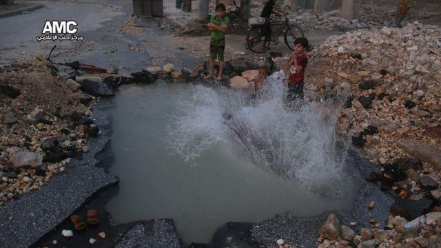 Niños juegan en Alepo en un cráter de una explosión