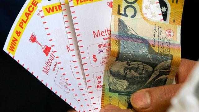 Человек держит в руке купюру и пачку чеков из австралийских игровых автоматов