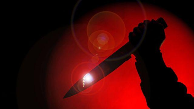 Una mano con un cuchillo en fondo rojo