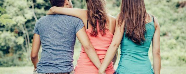 Homem abraçado a mulher e de mão dada com outra