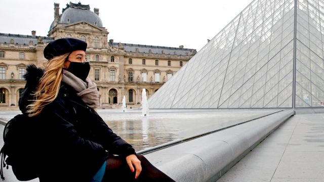 A women with a mask sitting in front of Louvre in Paris