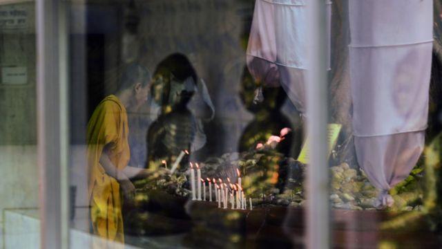 ঢাকায় একটি বৌদ্ধ মন্দিরে প্রার্থনা করছেন একজন ভান্তে।