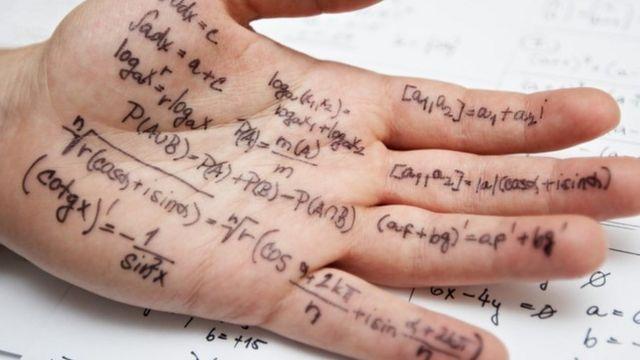 Un estudiante con fórmulas matemáticas escritas en la mano.