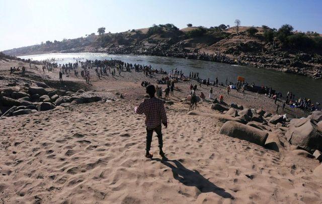 أعداد كبيرة من اللاجئين من إقليم تيغراي الإثيوبي تتجمع على ضفاف أحد الأنهار في السودان.