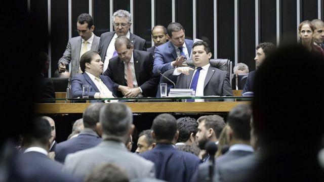 Ao centro, Rodrigo Maia e Davi Alcolumbre aparecem sentados em mesa no Plenário da Câmara, rodeados por parlamentares e assessores que falam com eles