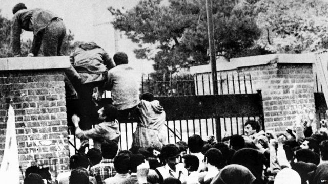 Iranian protesters scale a wall of the US embassy in Tehran on 4 November 1979