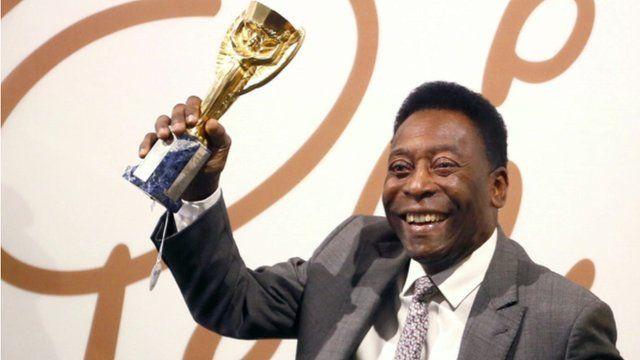 Pele holds a replica Jules Rimet trophy