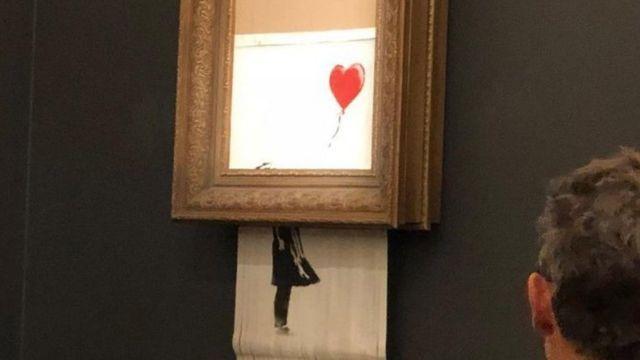 バンクシーが描いた少女と赤い風船の絵は、オークションで落札された後に「自壊」した