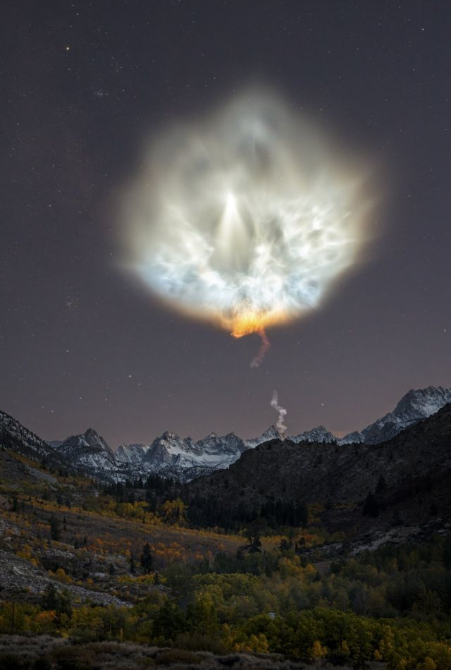 Landscape view of the smoke plume of a rocket, above mountains