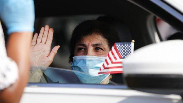 Una mujer hace el juramento en una ceremonia de naturalización en Estados Unidos desde un automóvil por motivo de la pandemia.