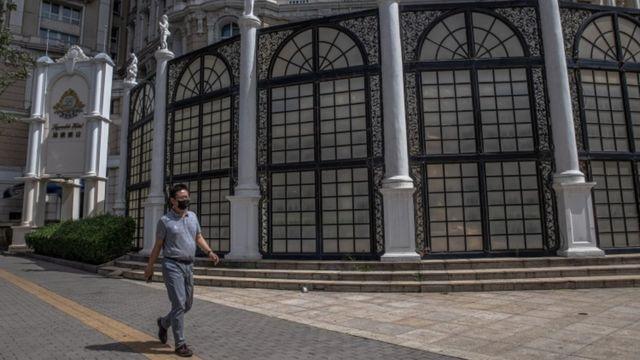 Homem com máscara caminha em frente a hotel suntuoso com portas fechadas
