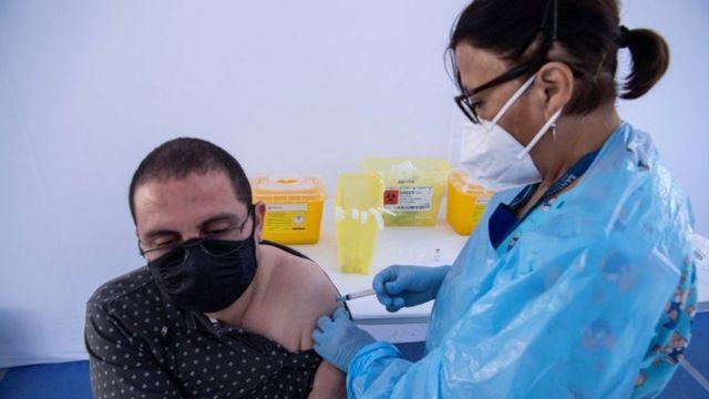 Un hombre es vacunado en Santiago de Chile.