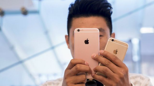 A man takes pictures as the Apple iPhone 6s and 6s Plus go on sale at an Apple Store in Beijing, China, September 25, 2015.