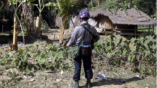An armed policeman stands guard at the ChainKharLe village during the visit of Yanghee Lee (not in picture), the United Nations Special Rapporteur on the situation of human rights in Myanmar, Rathedaung town, Rakhine State, western Myanmar, 14 January 2017