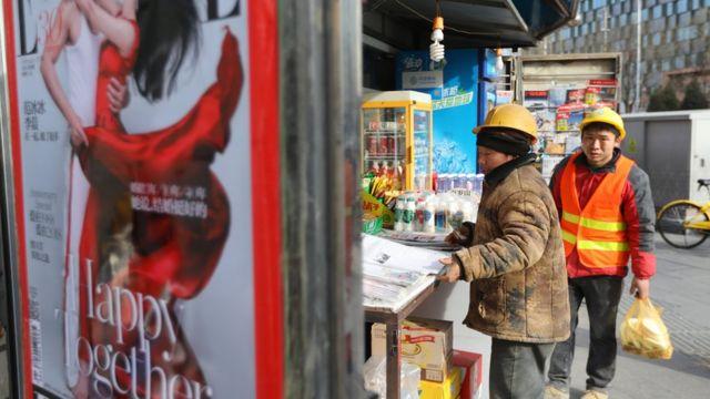 外來民工在報攤看報紙