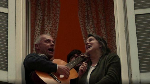 Pessoas cantando de janelas na Itália
