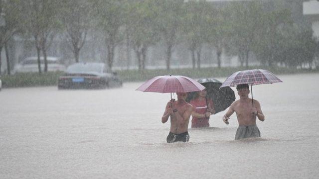 Zhengzhou kentinde insanlar sel sularında
