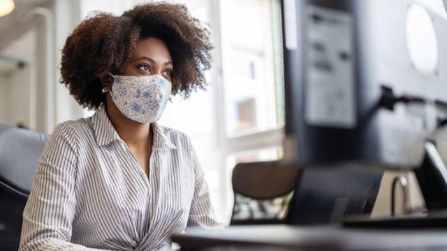 Mulher usando máscara no trabalho