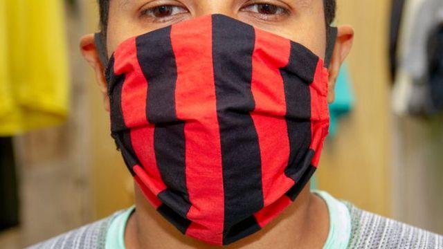 Foto do rosto de um homem, que usa uma máscara vermelha e preta