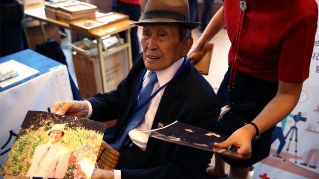 Stariji muškarac iz Južne Koreje sa porodičnim fotografijama