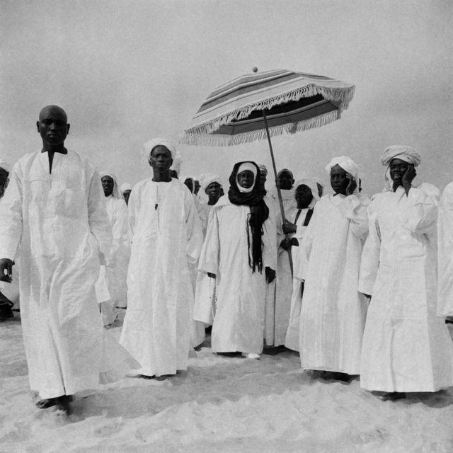 Des hommes vêtus de boubous blancs et de turbans marchent ensemble. L'un d'eux est protégé du soleil par un autre homme qui tient un parasol au-dessus de sa tête.