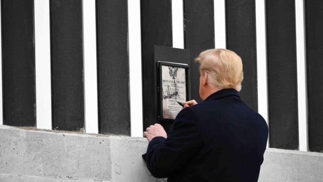Trump firmando el muro en la frontera con México.