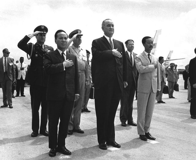 Front row, from left to right, Chairman Nguyen Van Thieu (1923 - 2001), President Lyndon B. Johnson (1908 - 1973) and Prime Minister Nguyen Cao Ky (1930 - 2011) salute during the playing of the American and Vietnamese national anthems at Guam's International Airport, Agana, March 20, 1967.