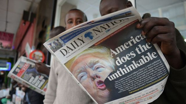 People read a Kenyan daily newspaper with the front page showing newly elected US President Donald Trump in Nairobi on November 10, 2016