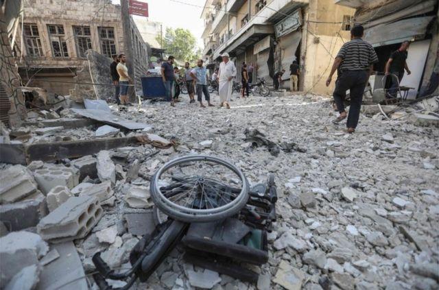 Uma cadeira de rodas em meio aos escombros dos edifícios destruídos em Ariha
