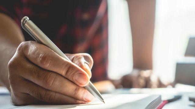 Pessoa escrevendo à mão