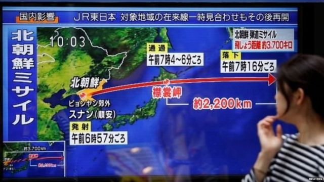 A passerby looks at a TV screen reporting news about North Korea's missile launch in Tokyo